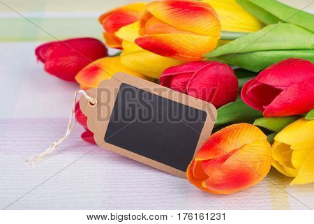 Colorful spring tulips with blank tag for copy space