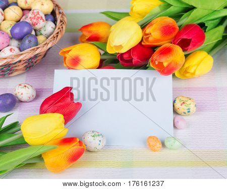 Colorful tulips and Easter candy around a blank envelope