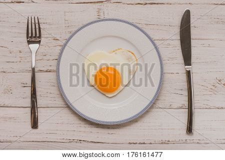 Fried eggs in the shape of heart on a white plate