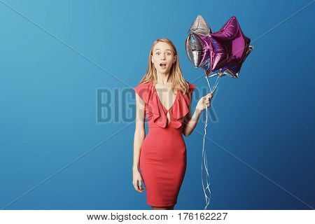 Valentine's Day. Woman in red dress holding balloons on the blue background. Processed with VSCO s3 preset