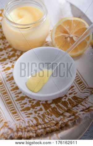 Lemon kurd with a spoon served on a table