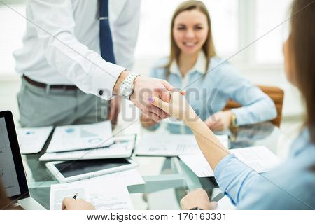 Bank Manager and the customer shake hands after signing a lucrative contract on the background of the modern office