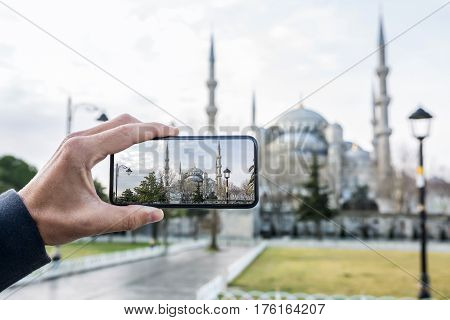 Male hand with a mobile phone takes a photo shoot of the Blue Mosque in Istanbul. Horizontal.