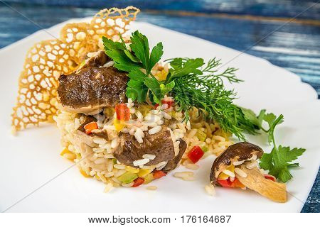 Risotto with porcini mushrooms and herbs on a white plate