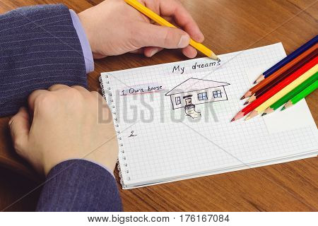 Man writes and draws own dream of house on the notepad with color pencils. concept of visualization future