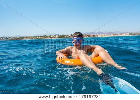 Smiling boy in swimming mask learns to swim on lifebuoy in the sea