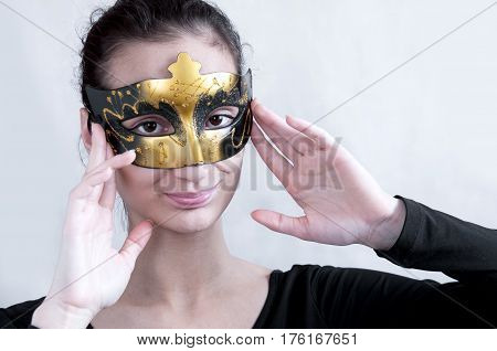 Girl Brunette In A Theatrical Mask Holding His Hands Behind His Head And Smiles