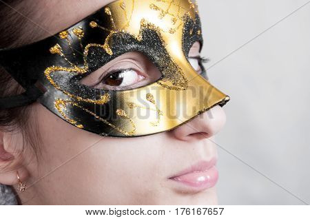 Portrait Of A Young Brunette Woman In A Theatrical Mask Side