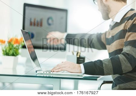Finance specialist working on laptop with financial charts and marketing schemes in the modern office