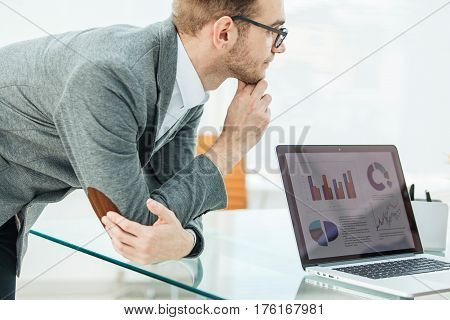Finance specialist looks at the screen of the laptop with financial charts the company's development .the photo has a empty space for your text.