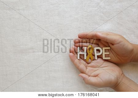 Hope with yellow gold ribbons on hands Sarcoma Awareness Bone cancer Liver cancer Bladder Cancer childhood cancer awareness