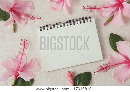 Notebook With Pink Hibiscus Flowers On Linen, Copy Space Background, Selective Focus, Vintage Tone