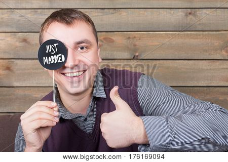 Man with funny icon on stick shows thumbs up sign