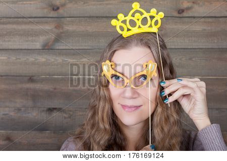 Woman with funny glasses and crown on a sticks