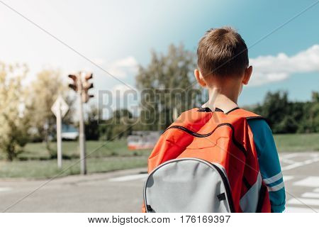 Schoolboy standing and waiting at zebra crossing