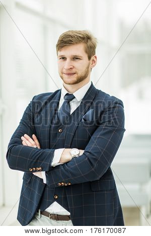 newcomer businessman in a business suit stands near the window, hands folded in front of him .the photo has a empty space for your text