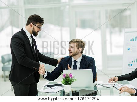 handshake Manager and the client before signing a contract in the workplace in a modern office.the photo has a empty space for your text