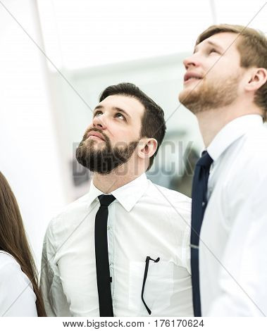 successful business team standing beside and looking up.the photo has a empty space for your text