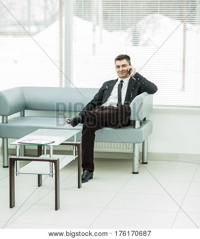 businessman sits in the lobby of a modern office and talking on the phone.the photo has a empty space for your text