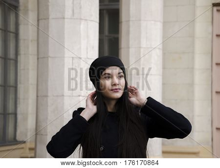 Spring cool day girl with beautiful make-up and long hair in a hat on a building background with columns