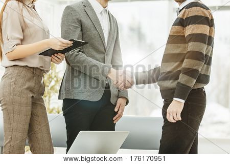 close-up of a handshake of a Manager and a customer on the background of the office