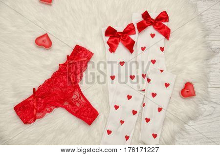 Fashion concept. Red thong panties and white stockings with bows candles in the shape of a heart on a white fur. View from above