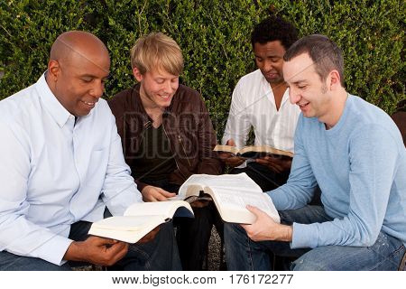Diverse group of men studying the Bible together.