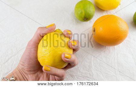 Female Hand Holding Lemon On A Table