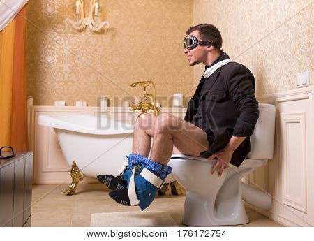 Man in pilot glasses sitting on the toilet bowl