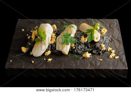 Black risotto with squid ink and seared calamary on wooden board, isolated on black