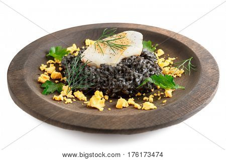 Black risotto with squid ink and seared calamar on wooden plate, isolated on white