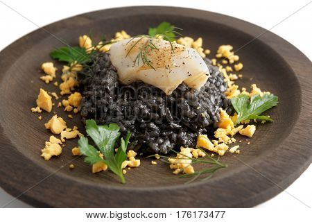 Black risotto dyed with squid ink and grilled calamary on round wooden plate
