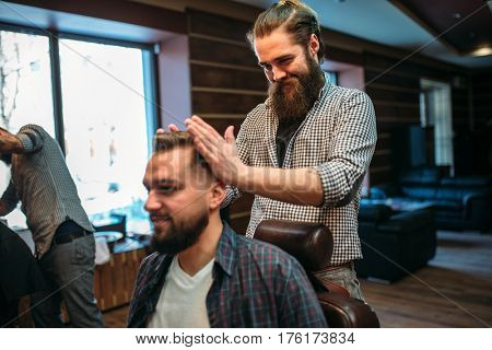 Coiffeur stacks hairstyle at hairdressing salon