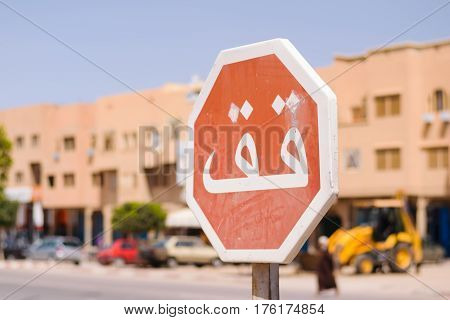 Image of a stop sign in focus and a blurred background whith arabic script in Morocco.