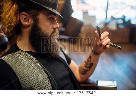 Bearded barber in hat with straight razor in hand