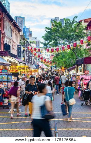 Singapore - December 12, 2014: Shoppers and tourists visit Singapore Chinatown for bargain souvenirs and authentic local food. The old colorful Victorian-style shophouses are a trademark of this popular area.