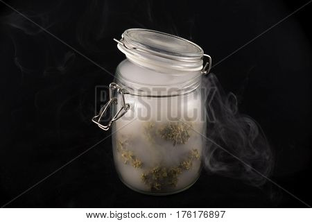 Detail of cannabis buds (maui skunk strain) on a glass jar with smoke isolated on black background - medical marijuana concept