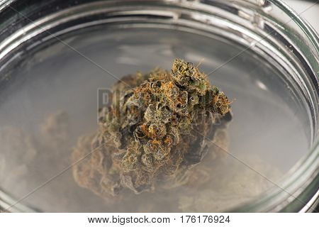 Macro detail of cannabis buds (maui skunk strain) on a glass jar with smoke - medical marijuana concept