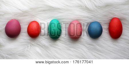 A variety of different sized and color painted Easter Eggs are lined up in a row on a white fur carpet background.