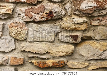 Close up on natural stone siding on the exterior wall of an old house.