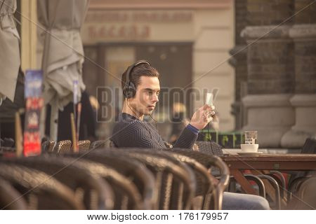 Young Man Using Smartphone Headphones Outdoors Coffee Table Chairs