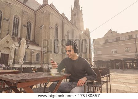 Young Man, Smartphone Headphones Coffee Outdoors Sunny Cathedral Smiling