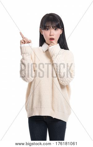 A studio portrait of a twenties Asian woman pointing at something