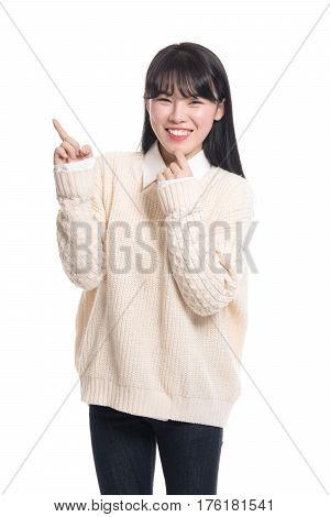 Studio portrait of twenties Asian woman pointing at something and being happy