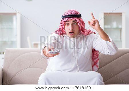 Arab man watching tv at home