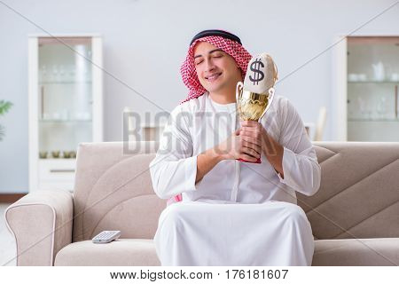 Arab man with prize and money on sofa