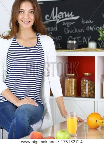 Portrait of a pretty woman sitting in the kitchen