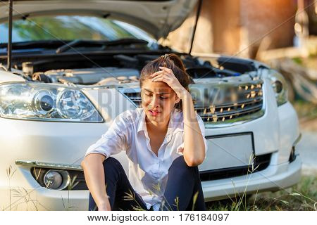 Young sad woman shouts holding his head sitting outside the car and she waits for assistance near her car broken down on the road side.