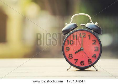Retro alarm clock on wooden table vintage style