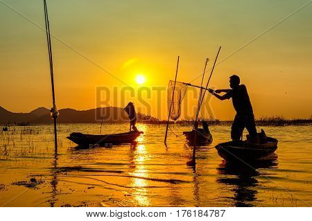 Silhouette Of Fishermen Using Nets To Catch Fish At The Lake During Sunset Time